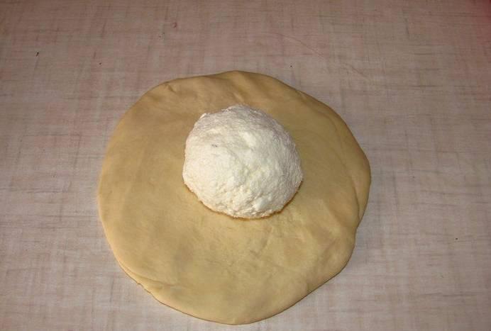 2. Раскатаем небольшую лепешку, по центру которой выкладываем начинку - перетертый творог, сулугуни или фету.