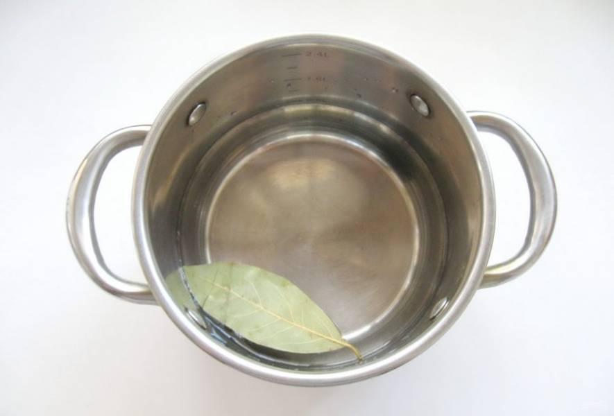 Приготовьте маринад для баклажанов. В кастрюлю налейте воду, добавьте лавровый лист.