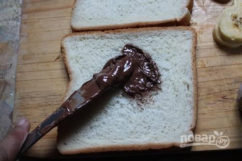 """На каждый ломтик хлеба нанесите по ложке """"Нутеллы""""."""