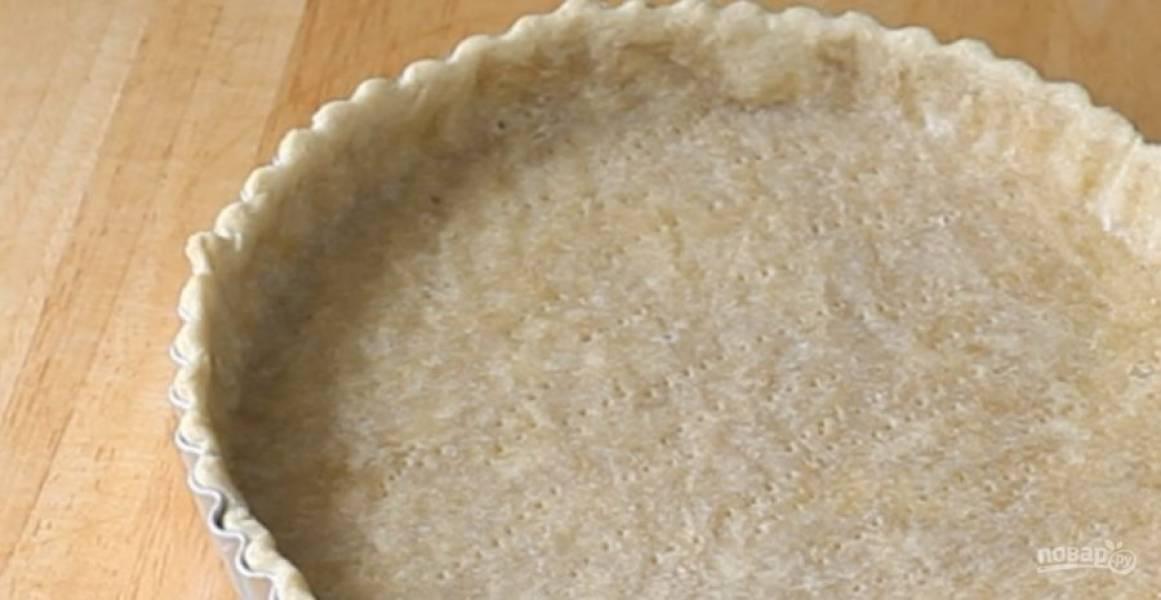 2.  Раскатайте тесто в пласт толщиной 5 мм и выложите его в форму, формируя бортики. Наколите тесто вилкой, накройте пергаментом и насыпьте груз. Выпекайте в разогретой до 180 градусов духовке 10 минут.