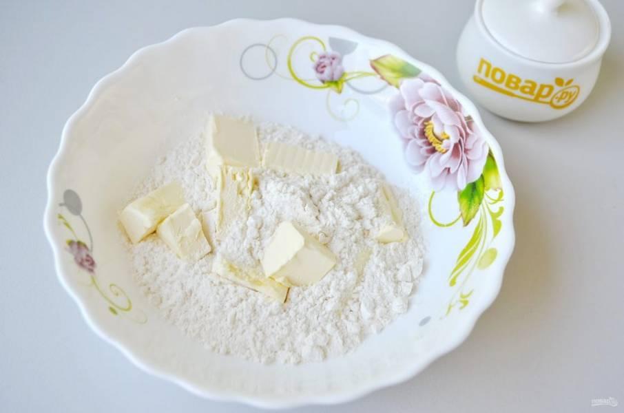 2. Возьмите глубокую посудину, всыпьте просеянную муку, добавьте порезанное холодной масло и разотрите его в крошку (это можно сделать ножом или вилочкой, как вам удобно).