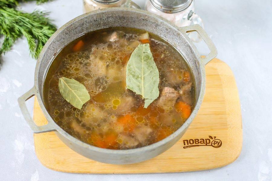 Затем влейте воду, добавьте соль и лавровые листья, отварите содержимое казана примерно 15 минут.