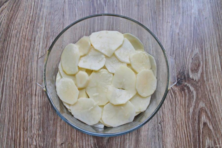 Форму для выпечки диаметром 24 сантиметра  смажьте растительным маслом и выложите на дно половину картофеля ровным слоем.