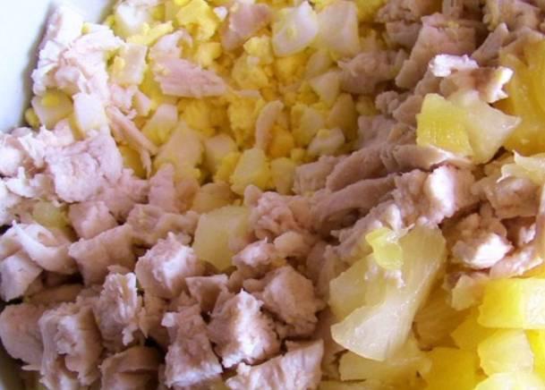 Вареные яйца и курицу нарезаем мелкими кубиками, также кубиками режем консервированный ананас.