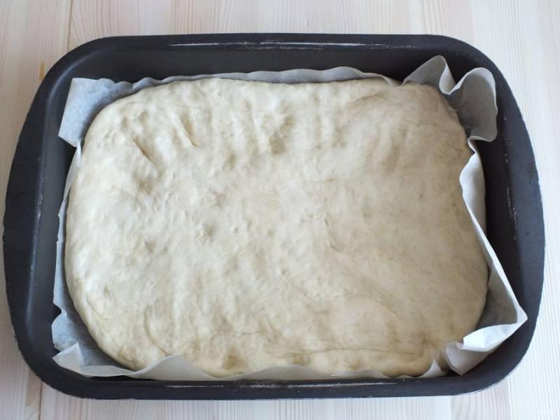 форму смажьте маслом или застелите пергаментом, переложите тесто, распределите по форме, чтобы не было зазоров, но бортики не делайте. Оставьте на 20 минут.