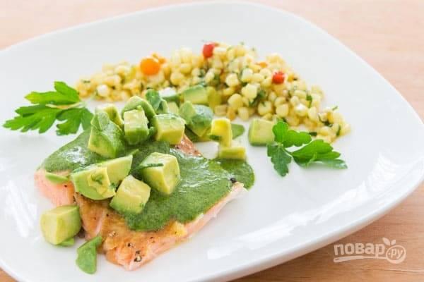 3.Очистите авокадо и удалите косточку, нарежьте его небольшими кусочками. Готовую рыбку немного остудите, затем нарежьте кусочками и полейте зеленым соусом, украсьте авокадо и подавайте.
