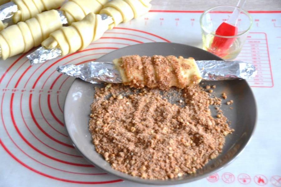 Смажьте заготовки из теста яичным белком и обваляйте в подготовленной сахарно-ореховой смеси.