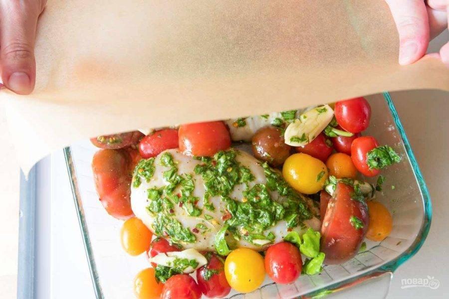 Духовку нагрейте до 200 градусов. Выложите курицу в форму, смешайте помидоры с маслом, перцем, солью. Крупные помидоры разрежьте. Выложите овощи в форму, накройте пергаментом.