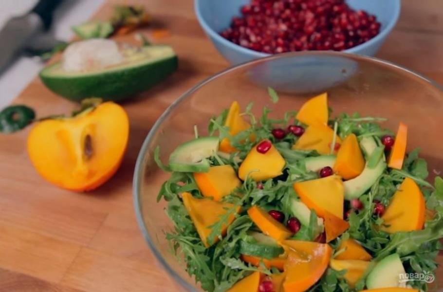 2. Выложите авокадо на нарезанную рукколу. Далее очистите хурму от косточек и листьев и нарежьте небольшими кусочками. Выложите ее на рукколу и посыпьте салат зернами граната.