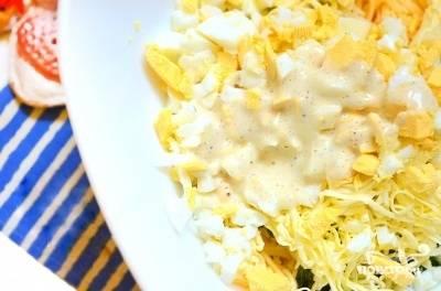 3.Сильно охлажденное сливочное масло (можно положить его минут на 15 в морозилку) натрите на мелкой тёрке. Также добавьте его к салату. Посолите по вкусу и перемешайте. Заправьте майонезом, предварительно смешав его с черным молотым перцем. Сырный салат с яйцом готов! Приятного аппетита!