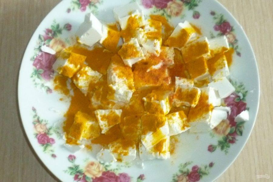 Фету нарежьте кубиками или крупными кусочками, посыпьте куркумой и красным перцем.