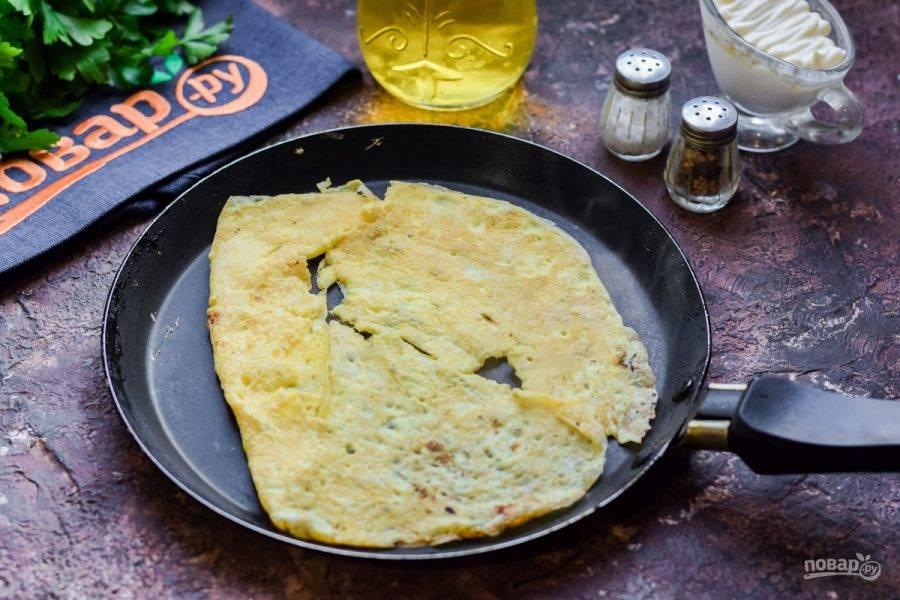 Перелейте яичную массу на смазанную маслом сковороду, жарьте омлет по минуте с каждой стороны.