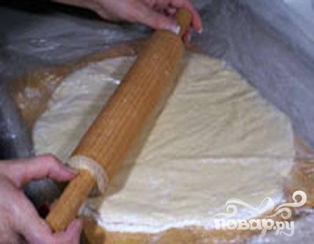 2.Между двумя слоями пленки толщиной пять миллиметров раскатываем в круглый пласт тесто.