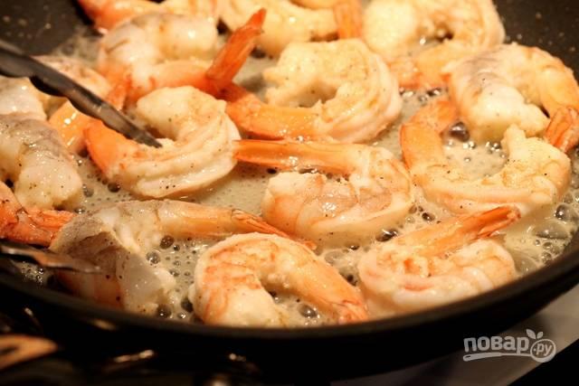 Добавьте сухой чеснок и перец. Помешивайте креветки лопаткой.