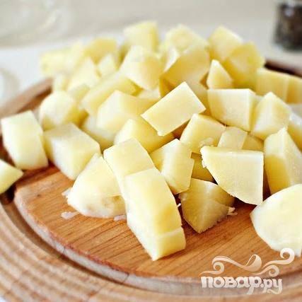 2. Очищенный картофель разрезать пополам и поместить в большую кастрюлю с водой, чтобы вода полностью покрывала картофель. Довести до кипения на среднем огне, затем снизить огонь до медленного и варить от 10 до 12 минут. Слить воду, откинув картофель на дуршлаг, и залить холодной водой. Остывший картофель нарезать кубиками размером 1 см.