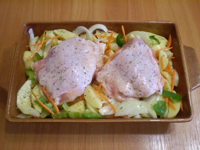 Сверху уложите куриные бедрышки. Отправьте в духовку на 50 минут. Температура запекания — 220 градусов.