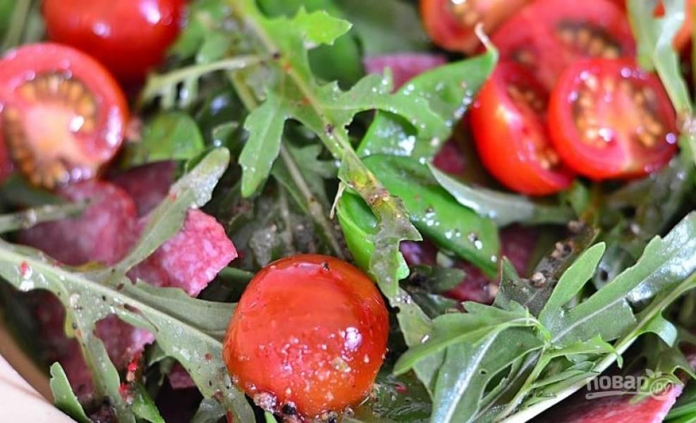 Выложите в миску вымытый и обсушенный салат, затем помидоры, горошек и яйца. Добавьте тонкие ломтики копченой колбасы и заправьте все смесью из оливкового масла и винного уксуса. Посолите и поперчите, тщательно все перемешайте.