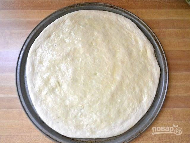 5.Сформируйте основу под пиццу по форме для запекания. Смажьте тесто оливковым маслом.