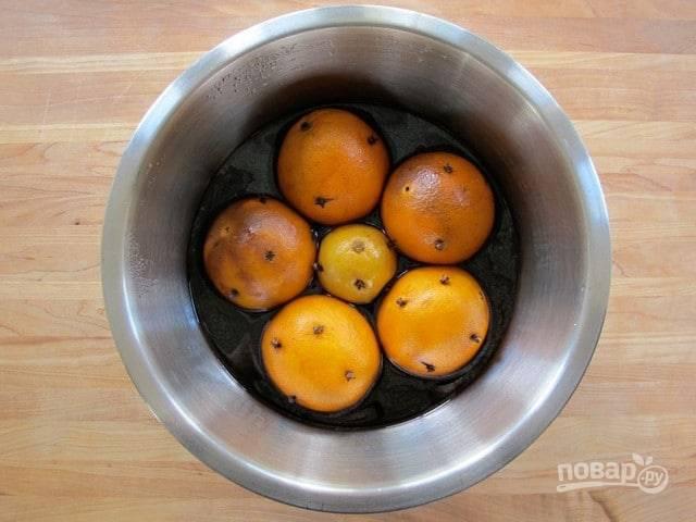 Далее в глубокую посуду выложите готовые апельсины с лимоном. Сверху влейте винную смесь. Закройте всё полотенцем. Уберите посуду на 1 сутки в тёплое место.