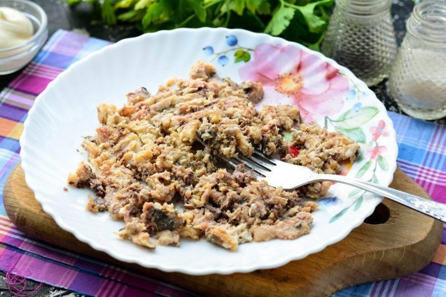 Слейте масло с сардин, удалите из кусочков крупные кости, измельчите рыбу вилкой.