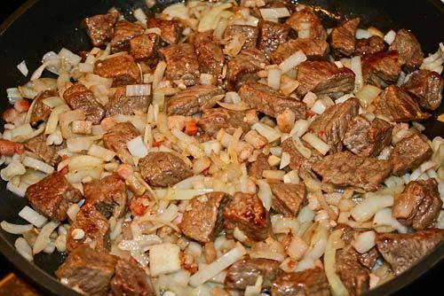 Говядину порежьте небольшими кусочками и обжарьте на сухой сковороде до полного испарения жидкости. Затем добавьте измельченный лук и чеснок, жарьте до полуготовности лука.