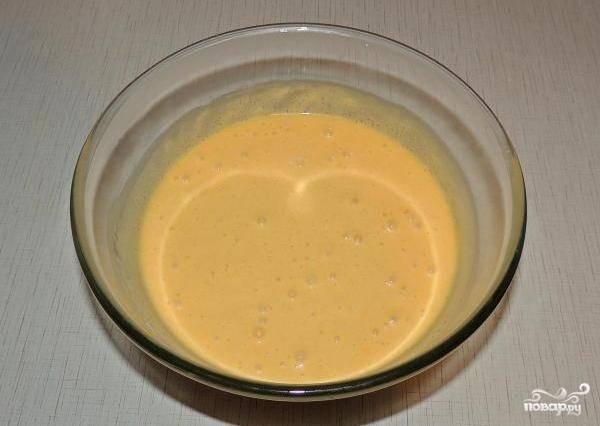 Отделяем 7 желтков от белков. Вливаем их в центр вместе с водой и подсолнечным маслом. Всё перемешиваем и взбиваем.