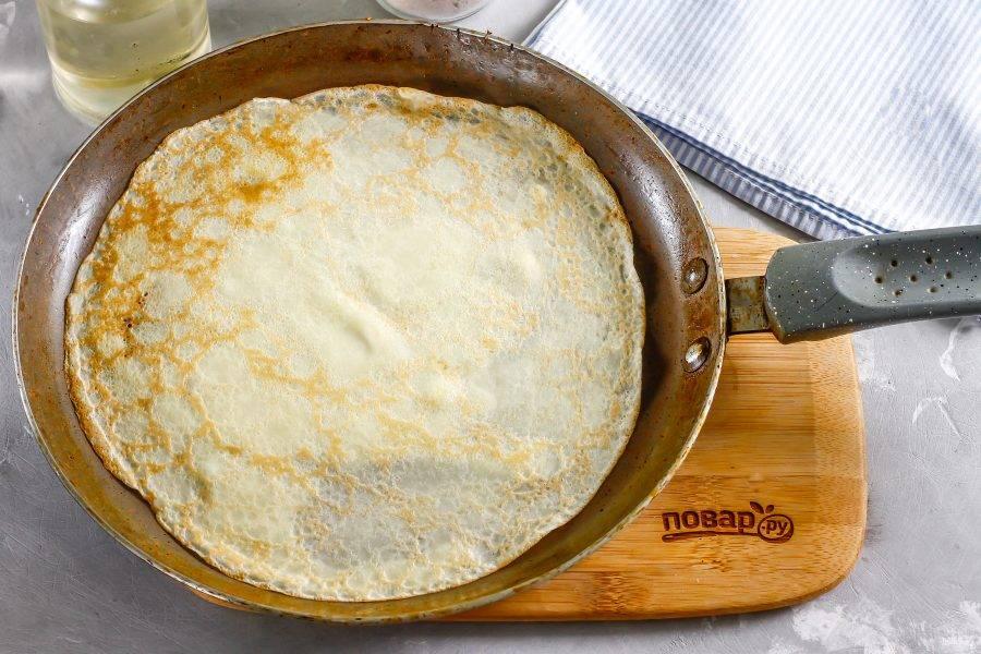 Прогрейте тонкую сковороду на плите, включая средний нагрев. Смажьте ее в первый раз салом или маслом, влейте часть теста и округлите его в виде блина. Обжарьте по минуте с каждой стороны до румяности.