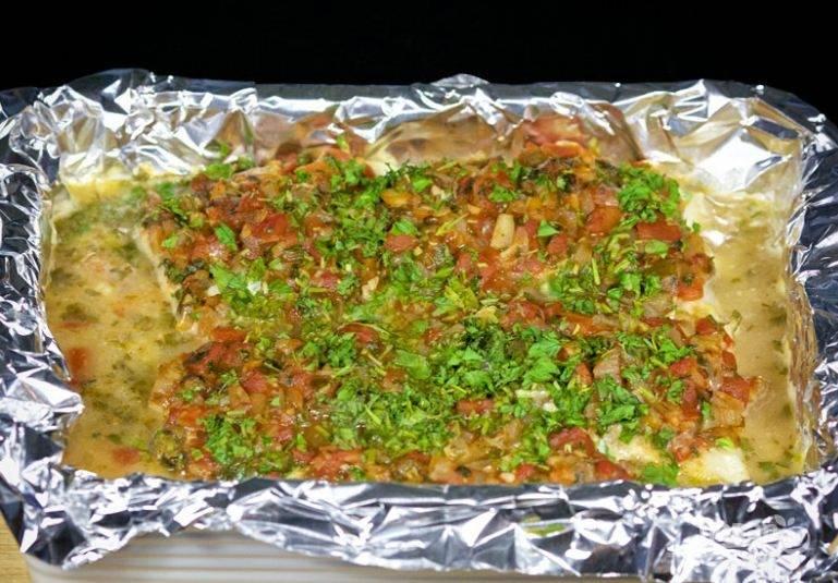 5.  Сверху на рыбу распределите овощную смесь. Посыпьте оставшейся зеленью и отправьте в духовку, разогретую до 240 градусов на 30 минут. Приятного аппетита!