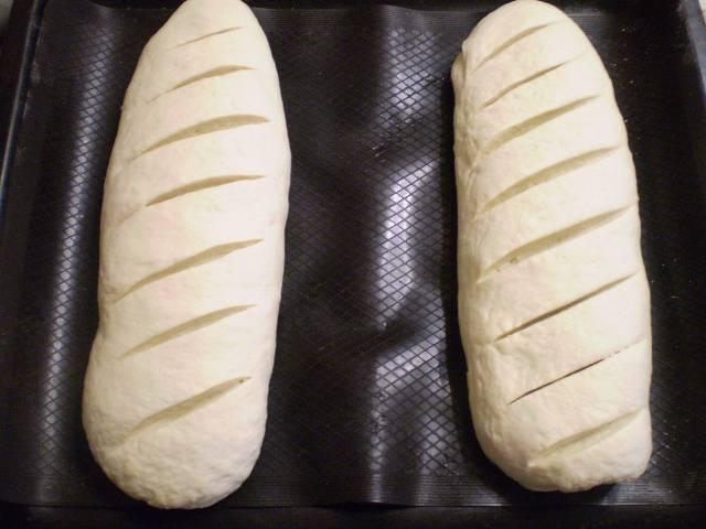 Разделите тесто на 2 части. Сформируйте батоны, сделайте острым ножом надрезы (неглубокие). Переложите батоны на противень, и дайте 20 минут расстойки.