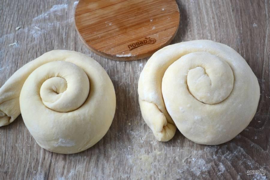 Скрутите тесто в тугой рулет, а затем рулет заверните в улитку. Вот такие две улитки должны получиться. Их переложите на разделочную доску, присыпанную мукой, накройте пищевой пленкой и отправьте в холодильник на 2 часа.