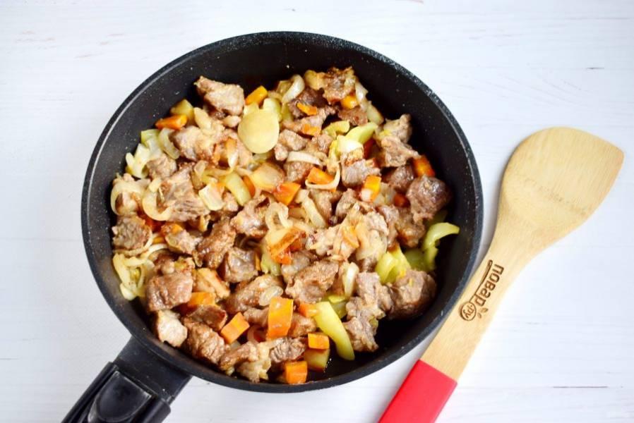 Мясо обваляйте в муке. Добавьте его в сковороду к овощам, обжаривайте до румяной корочки.