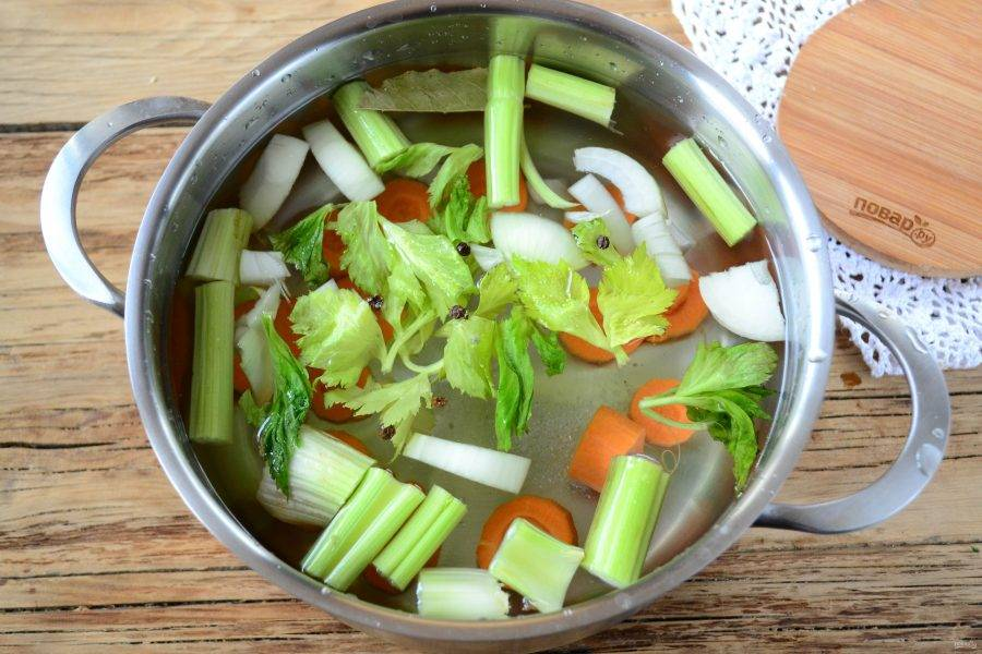 В кастрюльку налейте 1,5 л воды, поставьте на огонь. Отправьте туда половину моркови, нарезанной кружочками, половину лука, куски стеблей сельдерея, лавровый листик, перец горошком и соль. Все это доведите до кипения и поварите на медленном огне 20 минут.