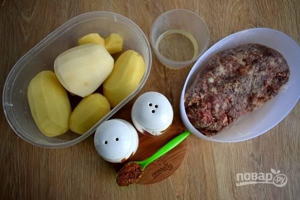 Подготовьте необходимые продукты. Картофель помойте и очистите. В фарш добавьте соль и специи, хорошо вымесите. Духовку разогрейте до 180 °C.