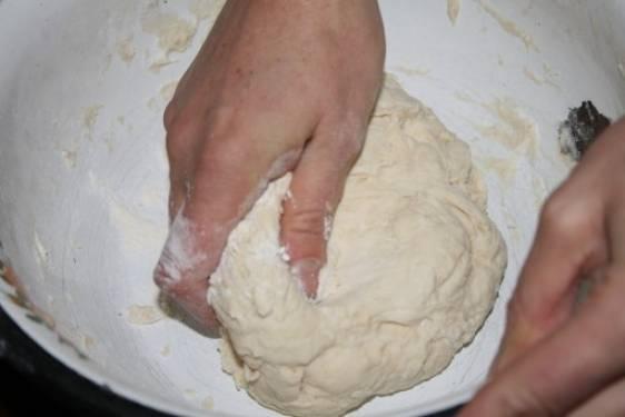 """2. Вливаем воду, а масло сливаем на руки над миской. Этими же """"маслеными"""" руками начинаем активно замешивать тесто."""