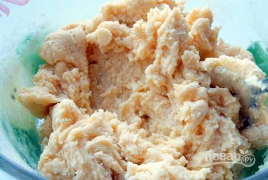Достаньте из холодильника сливочное масло, дайте ему постоять при комнатной температуре, чтобы оно стало мягким. Положите масло в миску, добавьте к нему сахарный песок и разотрите, пока масса не побелеет. Вбейте сырые куриные яйца, добавьте кукурузную и пшеничную муку, а также разрыхлитель. Тщательно перемешайте все ингредиенты и замесите мягкое тесто.