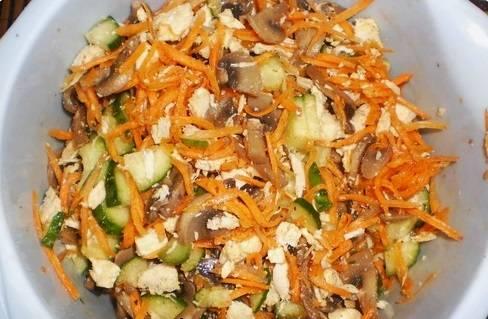 В миску выкладываем корейскую морковь, курицу, огурец и шампиньоны. Заправляем майонезом перед подачей на стол.
