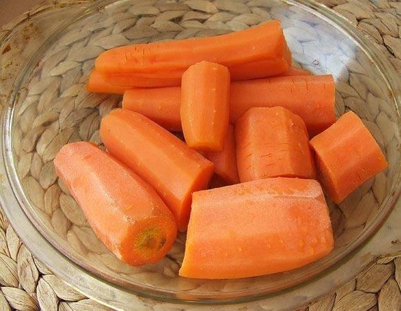 2. Пока набухает манка очистить, вымыть морковь и натереть ее на терке. Очень удобно использовать в рецепт приготовления морковных котлет на скорую руку подручную технику - кухонный комбайн, например. Это дополнительно сократит время.
