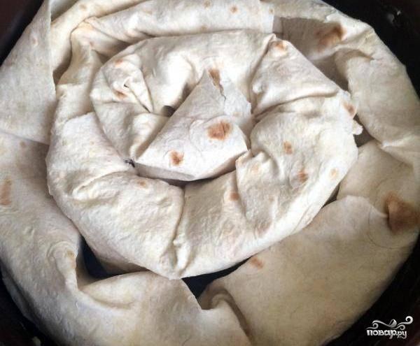 Круглую форму для выпечки смажьте маслом. Сверните лаваш в рулет и заверните его по кругу в форму. Внешне он будет напоминать улитку :)