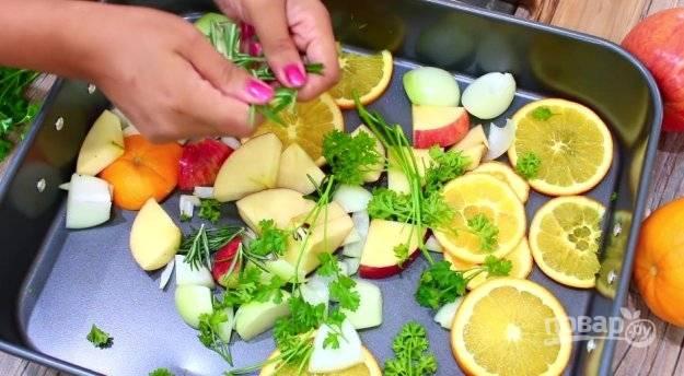 На дно противня уложите дольки яблок, лука и апельсина. Равномерно распределите розмарин и петрушку. Сверху уложите индейку. Свяжите её ножки и скрепите отверстие зубочистками или нитками.
