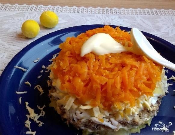 6. Натрите на терке со средними отверстиями сваренную и очищенную морковку. Выложите тертую морковку поверх слоя масла и сыра. На морковку выложите слой майонеза.