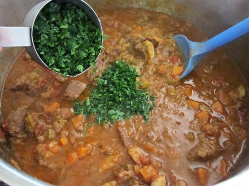 9. Когда мясное рагу с овощами в домашних условиях готово, добавить свежую измельченную зелень, перемешать и снять с огня.