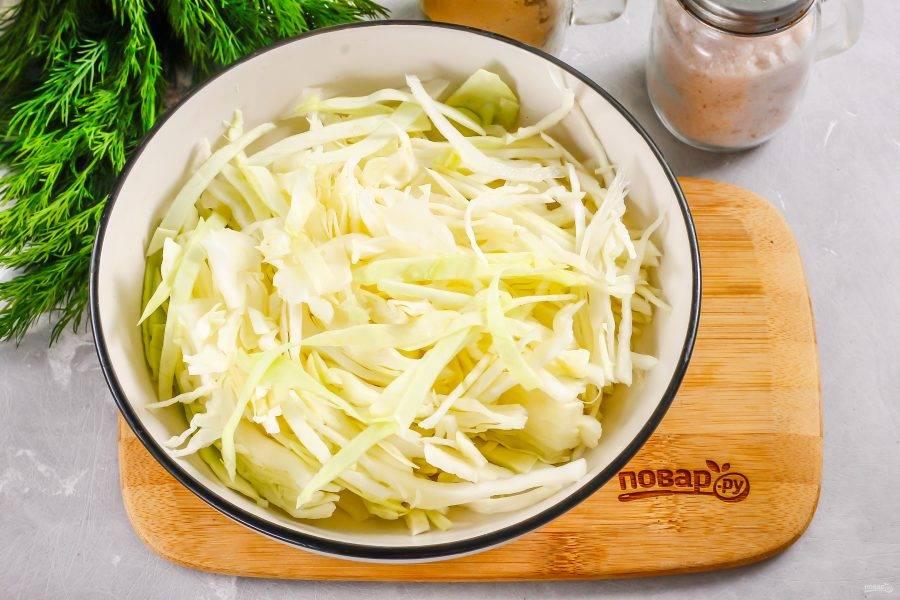 Белокочанную капусту нарежьте средними лентами и выложите в глубокую емкость. Посолите и помните нарезку руками, чтобы она выпустила сок.