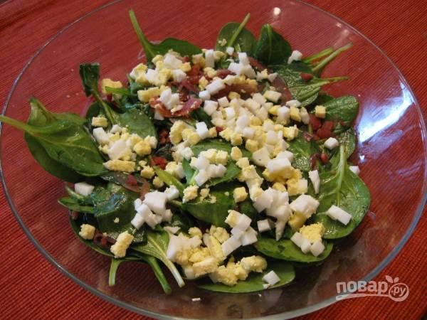 На шпинат вылейте маринад от лука и выложите сам лук. Мелко порежьте бекон, выложите в салат, а сверху посыпьте измельченным яйцом.