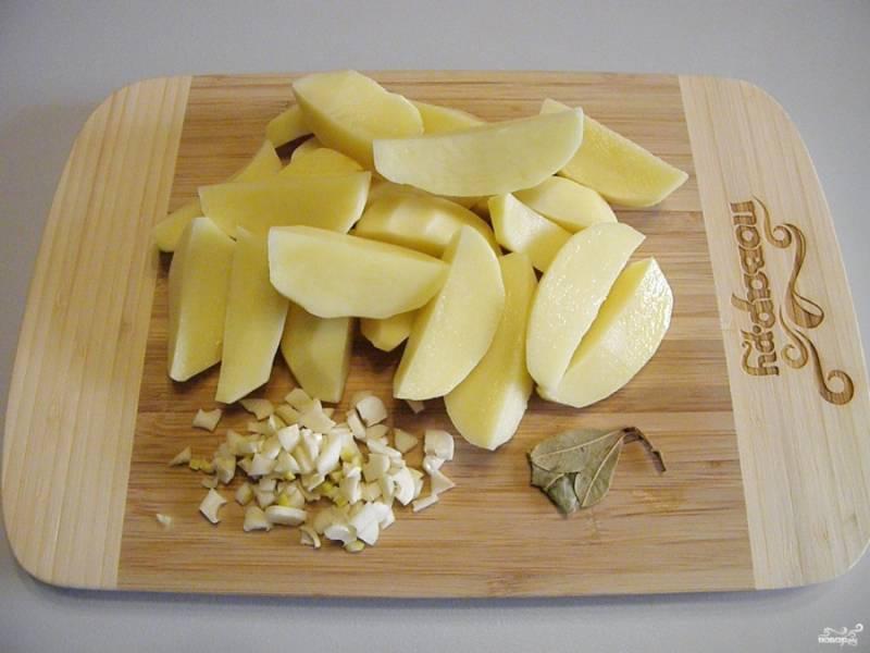 Порежьте крупно дольками очищенный картофель, чеснок порубите кубиками.