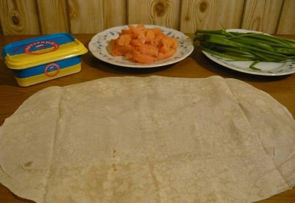 1. Для приготовления закуски с рыбой необходимо очистить филе семги от костей и кожи и нарезать небольшими кусочками. Лист лаваша развернуть на столе. Для удобства сразу можно положить под лаваш кусочек пищевой пленки.