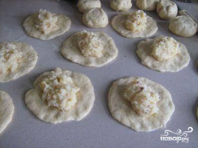 Из каждого кусочка делаем тонкую лепешку, в центр которой кладем немного картофельной начинки.