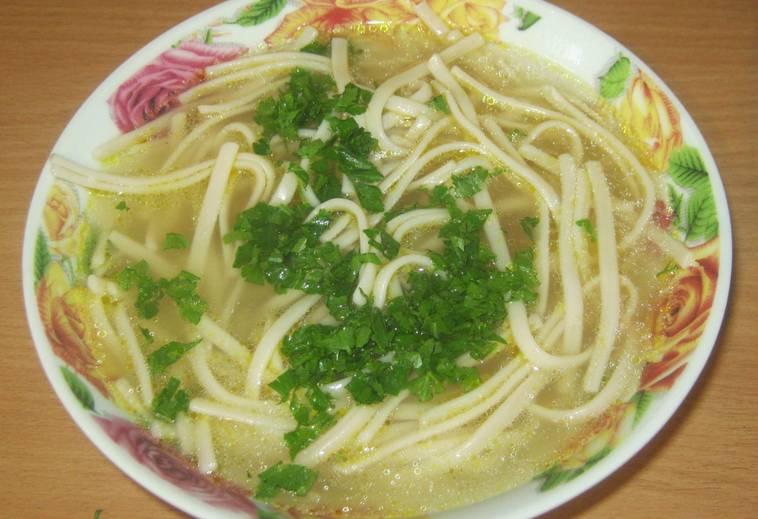 Перекладываем лапшу в глубокую тарелку, заливаем бульоном (морковь и лук уберите). Посыпаем измельченной зеленью, добавляем куриное мясо (по желанию). Приятного аппетита!