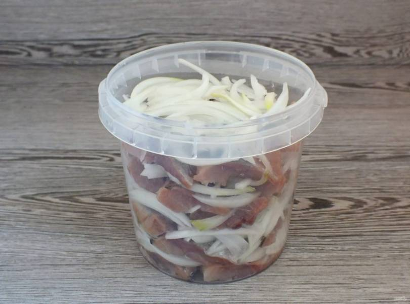 Возьмите просторную стеклянную или пластиковую тару. Сельдь нарежьте на кусочки. Выкладывайте в тару, чередуя слои селедки и лука.