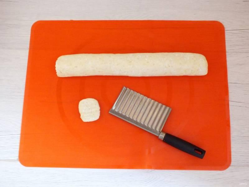 По истечении времени достаньте тесто. Скатайте валик, длинной примерно 30 см. Нарежьте с помощью ножа или резака кусочки теста, толщиной 0,5 см. Придайте округлую форму.