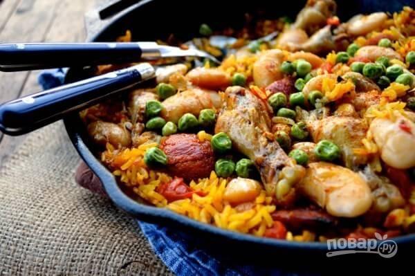 7. Влейте куриный бульон, добавьте бобы и соль, перец по вкусу. Встряхните сковороду, чтобы все ингредиенты перемешались. Доведите до кипения и уменьшите огонь. Сковороду накройте крышкой, готовьте 25 минут. Следите, чтобы смесь не была сухой и при необходимости доливайте бульон. В последние 5 минут готовки добавьте горошек. Готовьте до мягкости риса. Приятного аппетита!